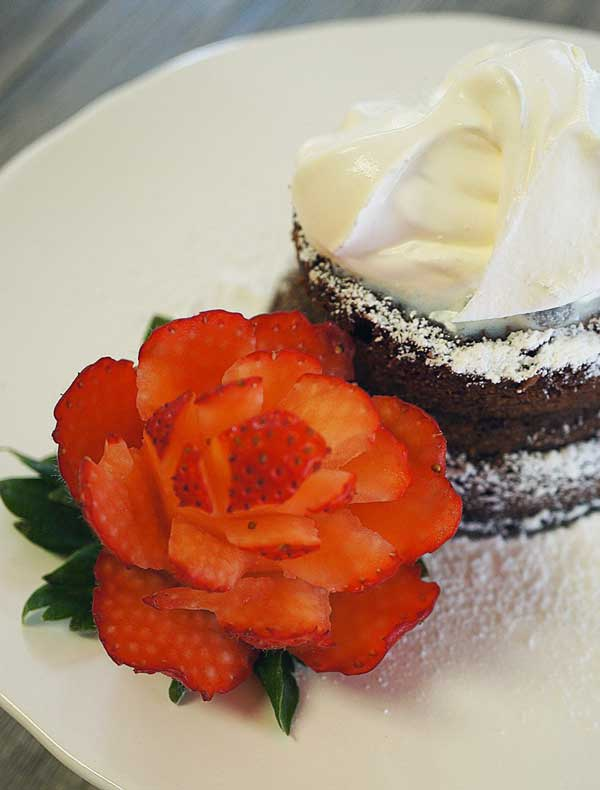 توت فرنگی تزئین شده در کنار تکه کیک