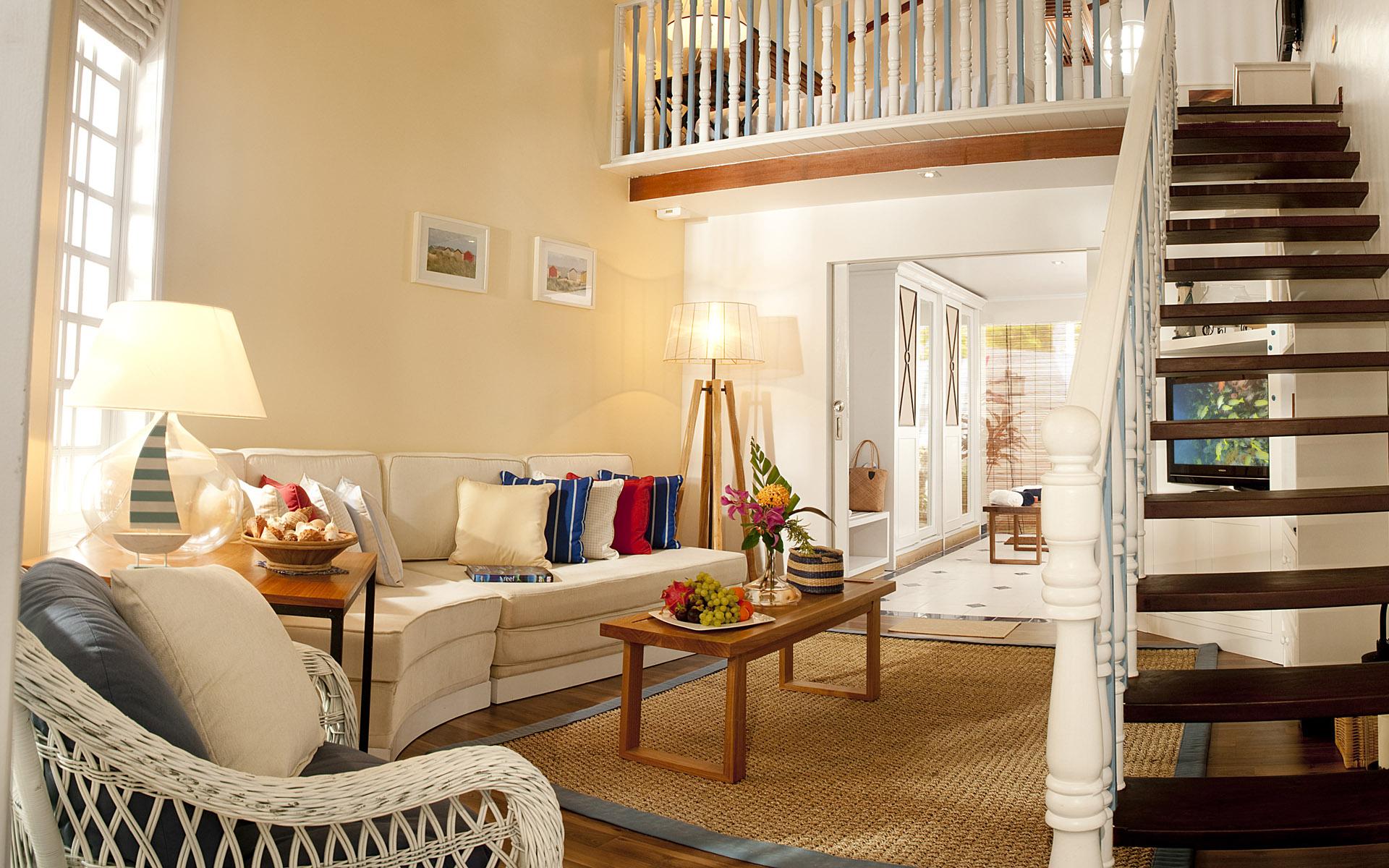 دکوراسیون اتاق نشیمن با طراحی کلاسیک به همراه راه پله چوبی و رنگبندی سفید و جذاب